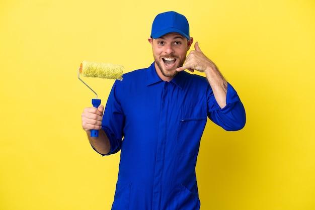 전화 제스처를 만드는 노란색 배경에 고립 화가 브라질 남자. 다시 전화주세요 기호