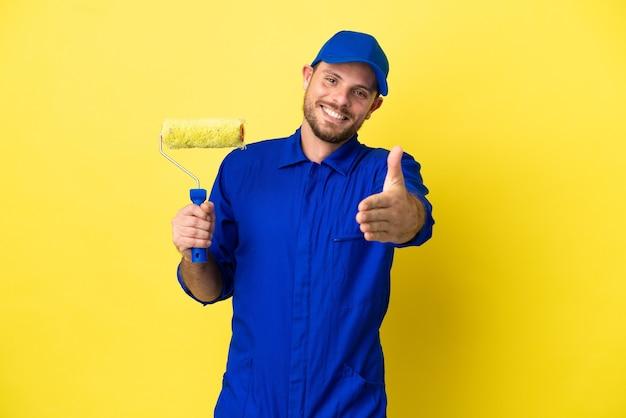 Художник бразильский мужчина изолирован на желтом фоне, пожимая руку для заключения хорошей сделки