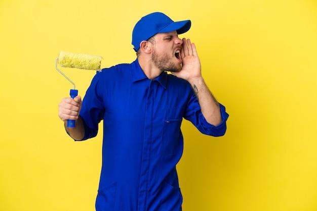 노란색 배경에 고립된 화가 브라질 남자는 입을 크게 벌리고 소리를 지른다