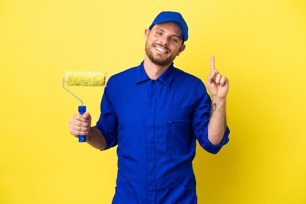 Художник бразильский мужчина изолирован на желтом фоне, показывая и поднимая палец в знак лучших