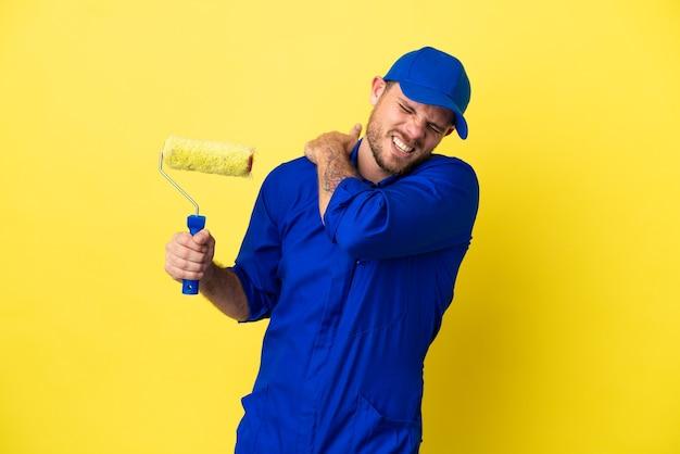 노란색 배경에 고립된 화가 브라질 남자는 노력을 해서 어깨 통증으로 고통받고 있다