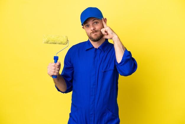 Художник бразильский мужчина изолирован на желтом фоне, думая об идее