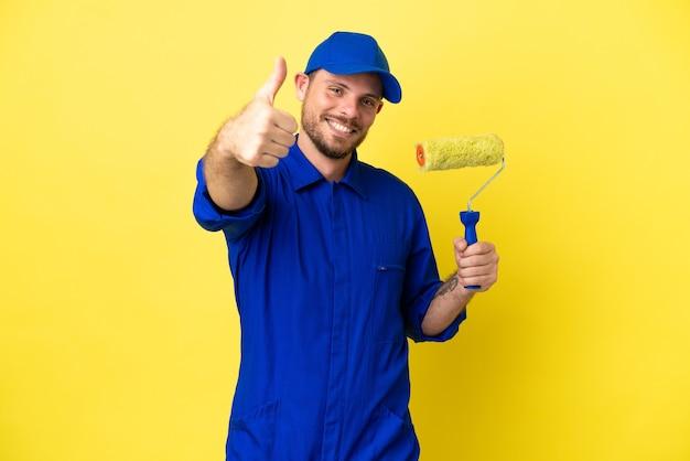 Художник бразильский мужчина изолирован на желтом фоне с большими пальцами руки вверх, потому что произошло что-то хорошее