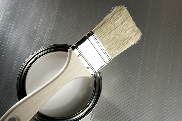 Painter brush and white paint tin