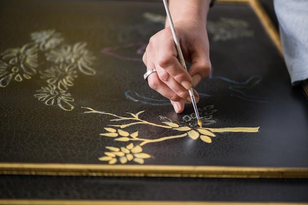画家の装飾工は木と葉のパターンを描きます