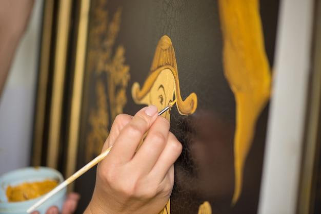 画家の装飾工は、葉と人間の中国のパターンを描く、マクロ撮影