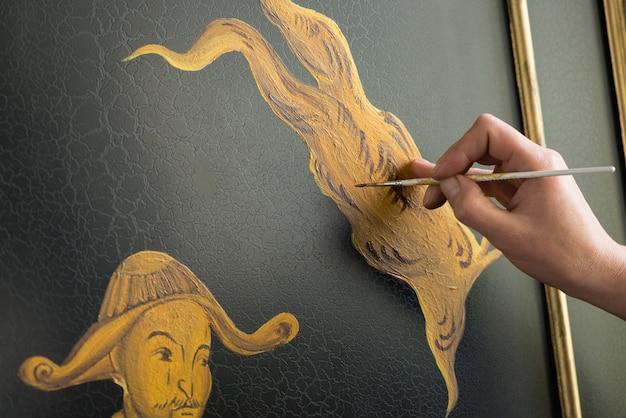 Художник-декоратор рисует узор тонкой кистью