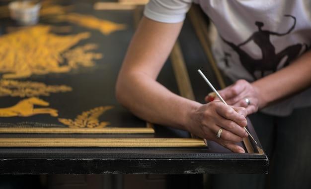 페인터 데코레이터는 얇은 브러시로 패턴을 그립니다.