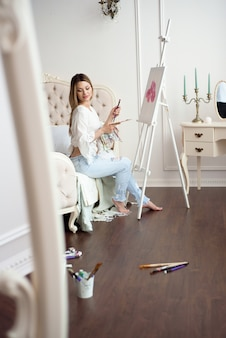 Painter drawing in art studio using easel. portrait of a young woman painting with oil paints on white canvas, side view portrait