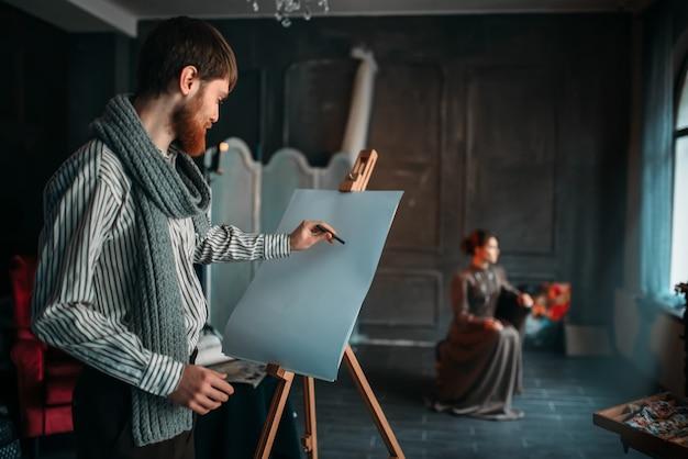 Painter drawing female portrait against easel in art studio. oil paint