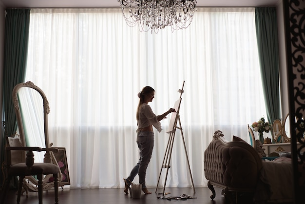 Художник рисует в художественной студии с помощью мольберта. портрет молодой женщины, живопись масляными красками на белом холсте, вид сбоку портрет