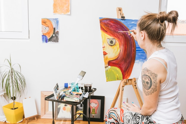 Painter drawing woman on canvas