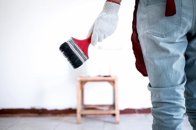 Painter hand in white glove painting wall with paint brush in room