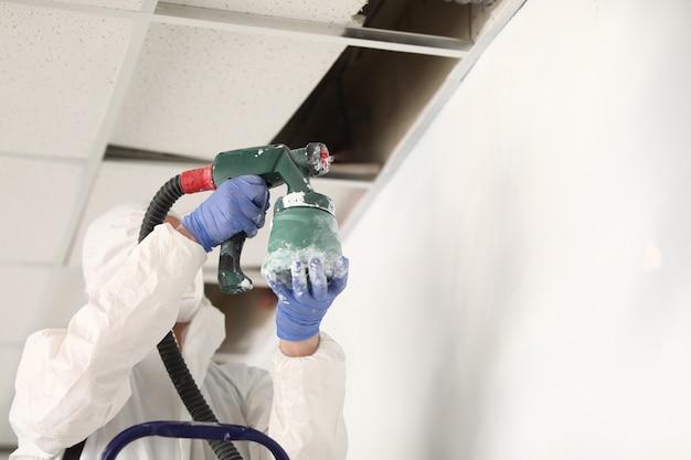 Художник держит зеленый пистолет-распылитель и красит стену под потолком в белый цвет.