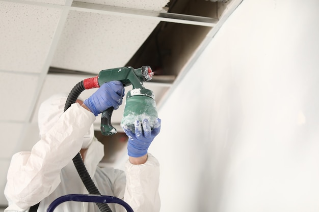 Painter hold green spray gun and paint wall white color under ceiling.