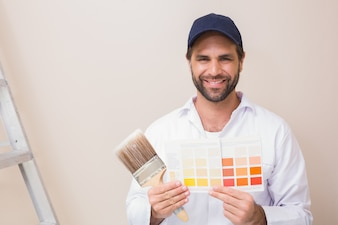 Painter holding a colour chart smiling at camera