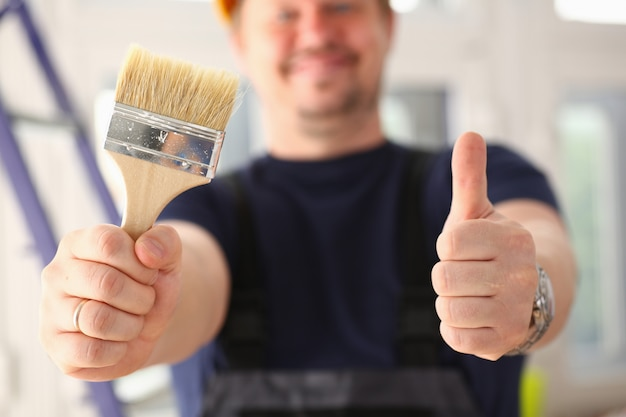 Painter holding brush and with thumb up