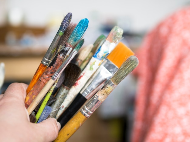 Painter holding messy brushes