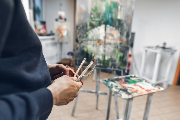 Painter holds a brush and a palette knife in the background of the easel with the host