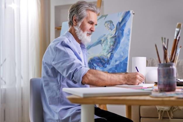 화가는 밝은 방에서 집에서 그림을 그리고 회색 수염을 가진 남자는 연필을 사용하여 걸작을 만들고 있습니다. 측면보기