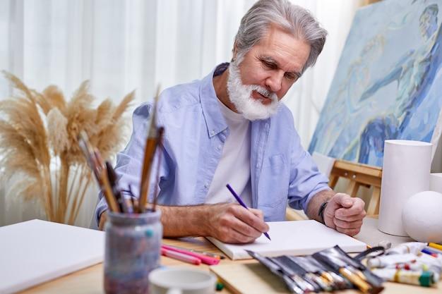 화가는 밝은 방에서 집에서 그림을 그리고 회색 수염을 가진 남자는 연필을 사용하여 걸작을 만들고 있습니다