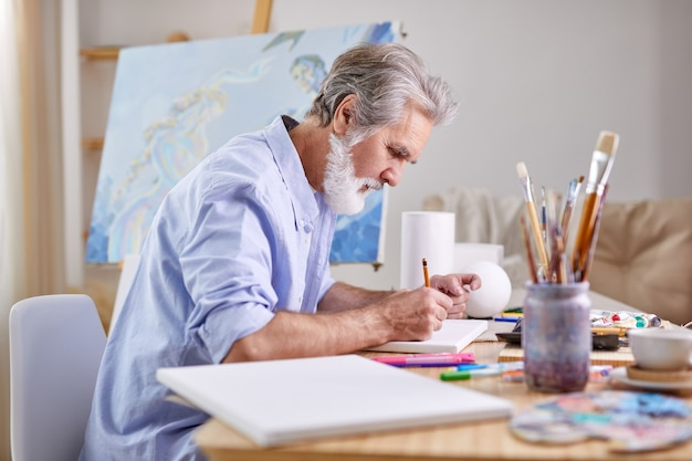 화가는 집에서 연필로 그림을 그리고 작업에 집중하고 파란색 셔츠를 입고 있습니다.