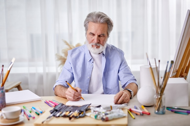 Painter is drawing at home using pencil, concentrated on work, wearing blue shirt.
