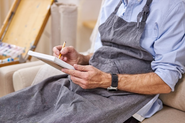 Painter male is drawing on small canvas with pencil, making sketch, sitting on sofa in apron. cropped