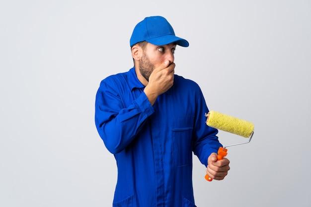 白いカバー口に分離されたペイントローラーを保持し、横を向いている画家の男