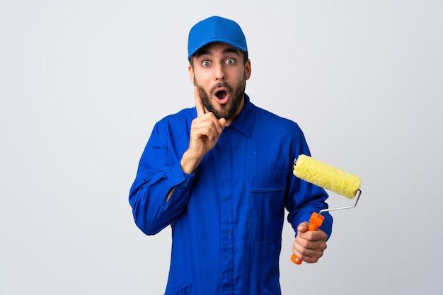 指を持ち上げながら解決策を実現しようとしている白い壁に分離されたペイントローラーを保持している画家の男
