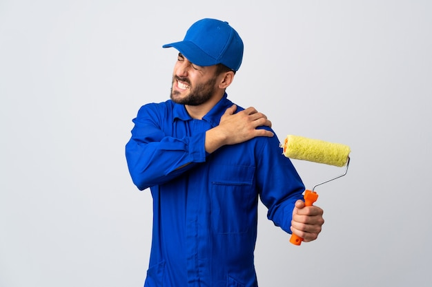 Painter man holding a paint roller suffering from pain in shoulder for having made an effort