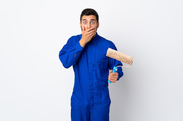 Painter man holding a paint roller on white wall covering mouth with hands