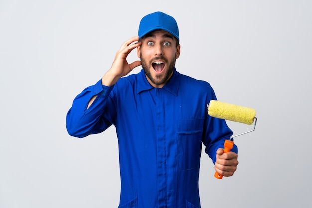 Painter man holding a paint roller with surprise expression