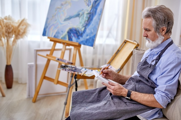 Painter man sitting on sofa drawing with pencil, wearing apron. in light studio room, work place