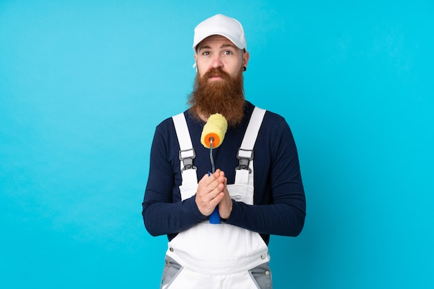 Painter man with long beard over isolated blue pleading