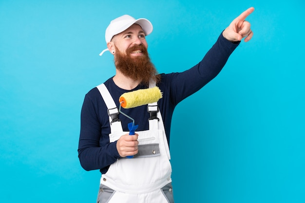 Painter man with long beard over isolated blue touching on transparent screen