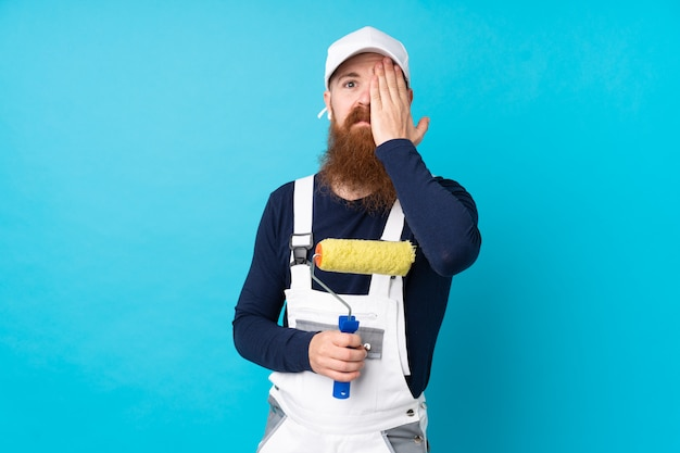Painter man with long beard over isolated blue wall covering a eye by hand