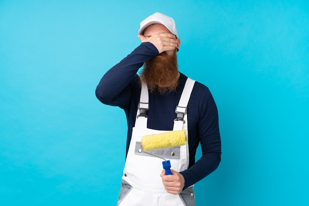 Painter man with long beard over isolated blue wall covering eyes by hands