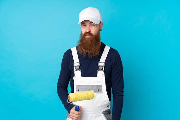 Painter man with long beard over isolated blue wall sad