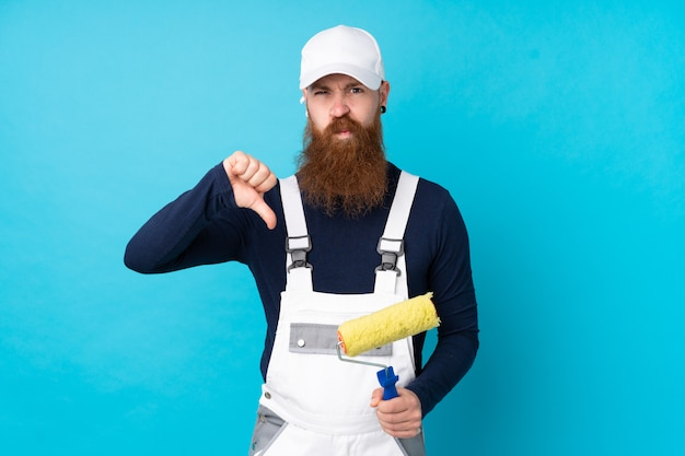 Painter man with long beard over isolated blue wall showing thumb down sign