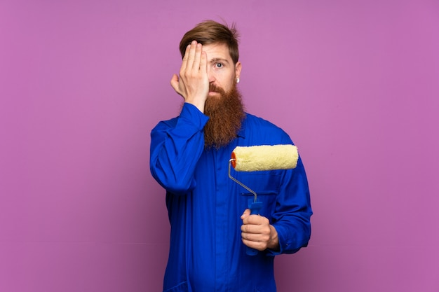 Painter man with long beard over isolated purple background covering a eye by hand
