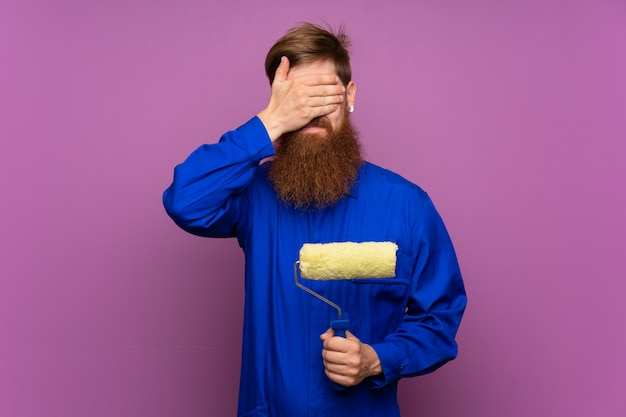 Painter man with long beard over isolated purple covering eyes by hands