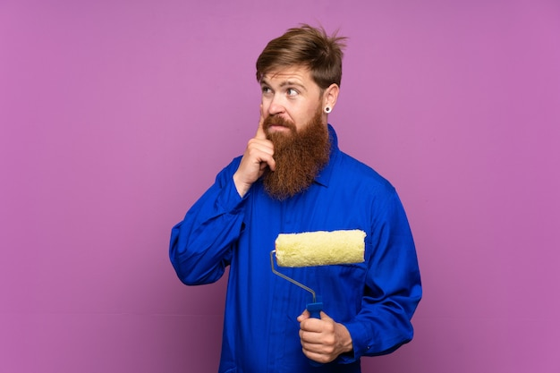 Painter man with long beard over isolated purple wall thinking an idea