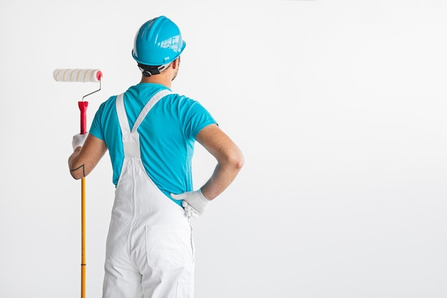 Painter in overalls with roller