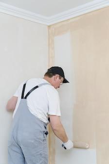 部屋の壁を描く画家
