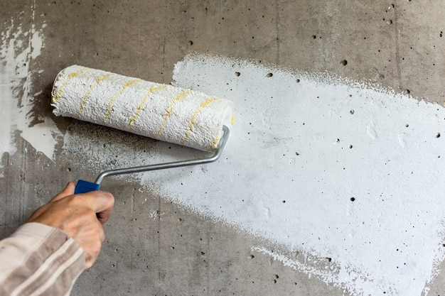 A painter paints a concrete wall with white paint, a male hand with a paint roller for painting a wall