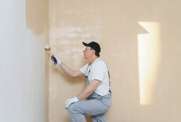 Painter paints a wall in the room.