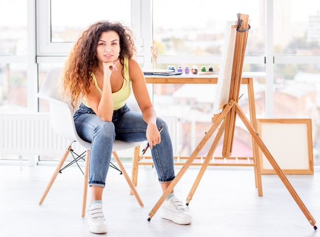 Painter sitting in front of easel