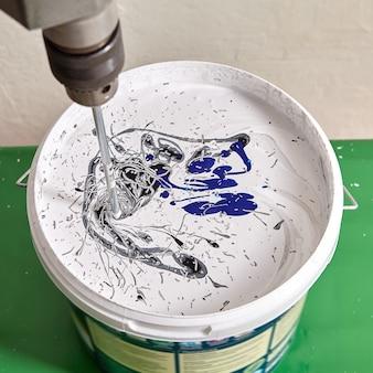 화가는 리노베이션 중 벽을 페인트하기 위해 양동이에 염료를 착색합니다.