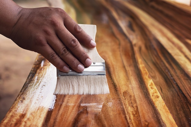 Painter uses paint plots to coat wood for beauty.